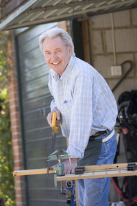 Man at shed sawing wood and smiling