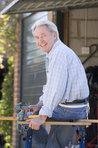 Man at shed sitting on tool bench smiling