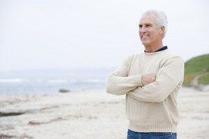 Man at the beach with arms crossed smiling