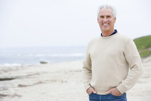 Man at the beach with hands in pockets smiling
