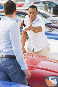 Man collecting new car from salesman on lot