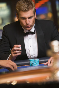 Man concentrating hard whilst gambling at roulette table in casino