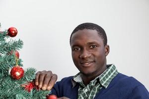 Man decorating the Christmas tree and looking at camera