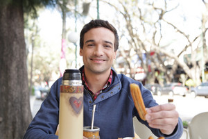 Man drinking Mate and eating a churro