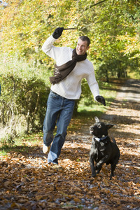 Man exercising dog in autumn woodland