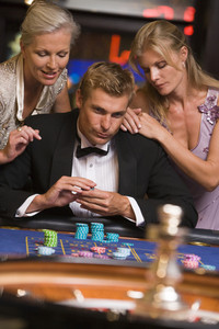 Man gambling at casino surrounded by glamorous women at roulette table