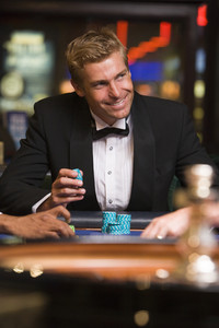 Man gambling at roulette table in casino looking confident