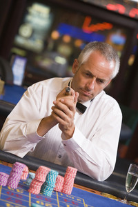 Man gambling at roulette table in casino