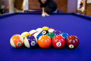 Man gets ready to begin breaking the rack of balls in a billiard game of 8 ball. Shallow depth of field with sharpest focus on the eight ball.