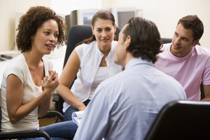 Man giving lecture to three people in computer room