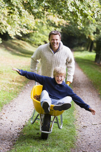 Man giving son ride in wheelbarrow on autumn path