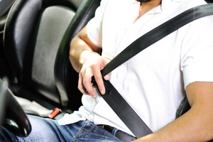 Man hand fastening a seat belt in the car