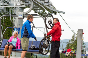 Man helping young couple taking down bicycle from chair lift