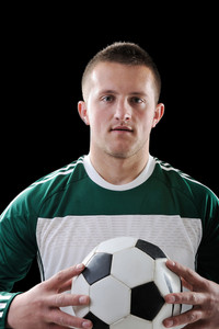 Man holding a football over black background