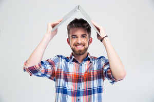 Man holding laptop on his head like roof of house