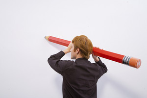 Man holding large pencil