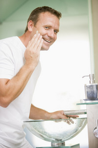 Man in bathroom applying shaving cream and smiling