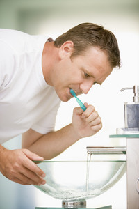 Man in bathroom brushing teeth