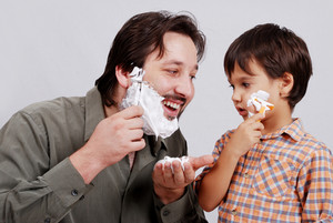 Man in bathroom putting shaving cream on young boy's face