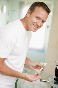Man in bathroom with hair gel smiling