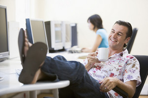 Man in computer room with feet up drinking coffee and smiling