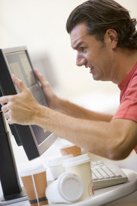 Man in computer room with many empty cups of coffee grabbing his monitor frustrated