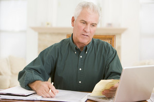 Man in dining room with laptop and paperwork looking unhappy