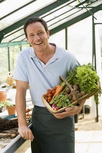 Man in greenhouse holding basket of vegetables smiling