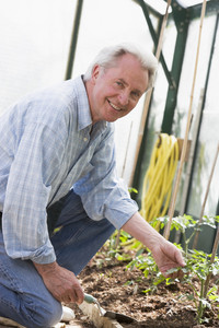 Man in greenhouse holding shovel smiling
