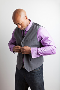 Man in his thirties getting dressed in business casual style buttons his vest.