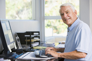 Man in home office using computer smiling