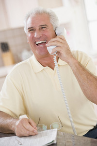 Man in kitchen on telephone laughing