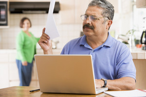 Man in kitchen with laptop and paperwork with woman in background