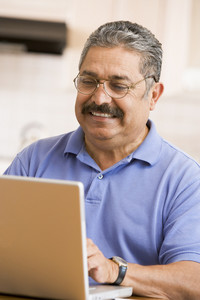 Man in kitchen with laptop smiling