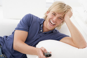 Man in living room holding remote control laughing