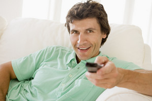 Man in living room holding remote control smiling