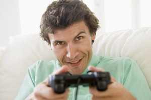 Man in living room playing videogames smiling