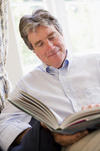 Man in living room reading book smiling