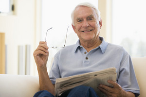 Man in living room reading newspaper smiling