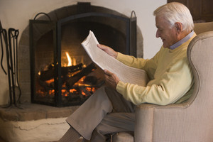 Man in living room reading newspaper