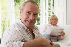 Man in living room smiling with woman in background reading newspaper