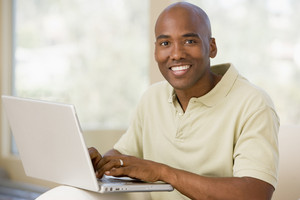 Man in living room using laptop and smiling
