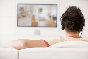 Man in living room watching television and wearing headphones