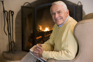 Man in living room with newspaper smiling