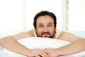 Man in sleeping bed, morning time
