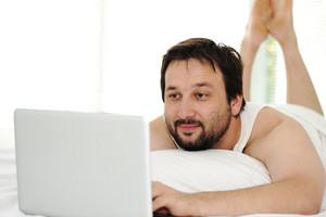 Man in sleeping bed using  laptop