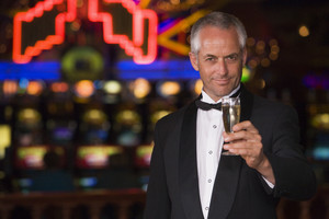 Man in tuxedo drinking champagne in casino proposing toast
