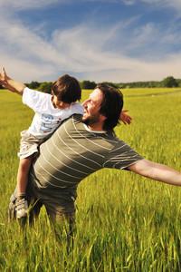 man in wheat field with boy