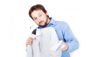 Man is holding two shirts and choosing to wear