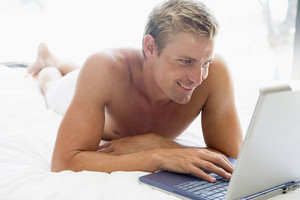 Man lying in bed with laptop smiling